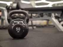50 lb kettlebell with a blurry bench and weight set in background royalty free stock images