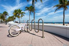 A lbike parked next to t Fort Lauderdale Beach Stock Image