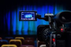 The LCD display on the camcorder. Shooting theatrical performances. The TV camera. Colorful chairs in the auditorium.  Royalty Free Stock Photo