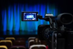 The LCD display on the camcorder. Shooting theatrical performances. The TV camera. Colorful chairs in the auditorium.  Royalty Free Stock Photos