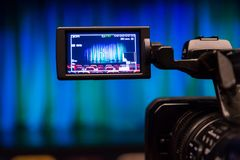 The LCD display on the camcorder. Videography in the theater. Blue-green curtain on the stage.  Stock Image
