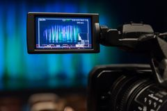 The LCD display on the camcorder. Videography in the theater. Blue-green curtain on the stage.  stock photos