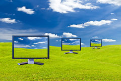 Lcd monitor on green grass meadow Stock Photos