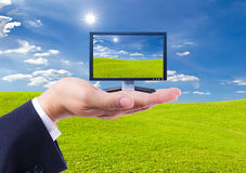 LCD Monitor in hand. On green grass meadow Royalty Free Stock Image