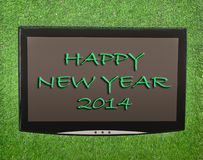 Lcd screen. On artificial green grass of happy new year 2014 Royalty Free Stock Photo