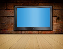 Lcd TV screen on brick wall and wood floor Stock Photos