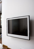LCD TV on A Wall. Modern LCD TV hung on a white wall of a house royalty free stock images