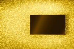 Lcd-TVpanel som hänger på den lyxiga guld- väggen Fotografering för Bildbyråer