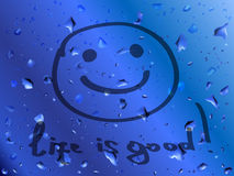 Lächeln. Das Leben ist gut. Aufschrift auf nassem Glas Lizenzfreies Stockbild