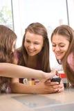 Lächeln mit drei junges weibliches Freunden Stockbilder