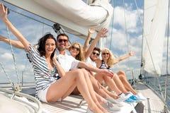 Lächelnde auf Yachtplattform sitzende und grüßende Freunde Lizenzfreie Stockfotografie