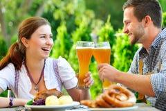 Lächelnde bayerische Paare bei Oktoberfest Stockbilder