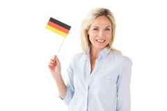Lächelnde Blondine, die deutsche Flagge halten Stockbild