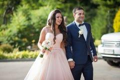 Lächelnde Braut mit einem Blumenstrauß und glücklicher Bräutigam, der zum wedd geht Stockbild