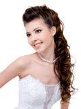 Lächelnde Braut mit lockiger Hochzeitsfrisur Lizenzfreies Stockfoto