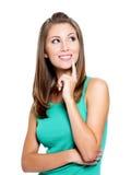 Lächelnde denkende Frau, die oben schaut Stockbilder