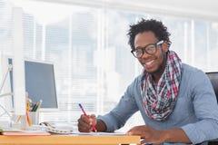 Lächelnde Designerzeichnung mit einem roten Bleistift auf einem Schreibtisch Stockfotografie