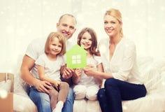 Lächelnde Eltern und zwei kleine Mädchen am neuen Haus Stockfoto