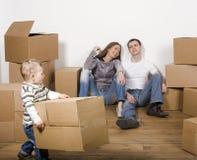 Lächelnde Familie im neuen Haus, das mit Kästen spielt Stockbild