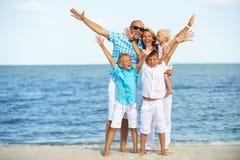 Lächelnde Familie mit den Kindern, die Spaß auf dem Strand haben Stockfoto