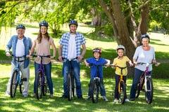 Lächelnde Familie mit ihren Fahrrädern Stockfotografie