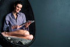 Lächelnde Frau auf Blasenstuhl-Lesezeitschrift Stockbild