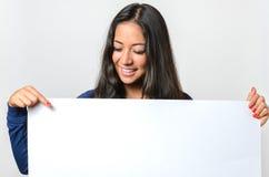 Lächelnde Frau, die auf ein leeres weißes Zeichen zeigt Stockbilder