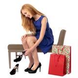 Lächelnde Frau, die auf einem neuen Paar Schuhen entscheidet Lizenzfreie Stockfotos