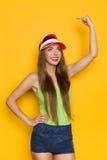 Lächelnde Frau, die auf gelben Kopien-Raum zeigt Stockbilder
