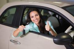 Lächelnde Frau, die Autoschlüssel bei Daumen aufgeben hält Stockfotografie