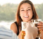 Lächelnde Frau, die Bier in der äußeren Einstellung hält Stockfotografie