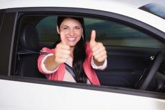 Lächelnde Frau, die Daumen oben in ihrem Auto gibt Stockbild