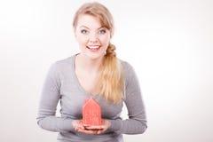Lächelnde Frau, die Hausmodell hält Stockbild