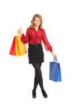 Lächelnde Frau, die mit Einkaufstasche aufwirft Stockbilder