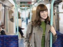Lächelnde Frau, die Stange im Nahverkehrszug hält Stockfoto
