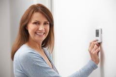 Lächelnde Frau, die Thermostat auf Hausheizungs-Heizsystem justiert Stockfotos