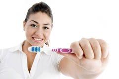 Lächelnde Frau, die Zahnbürste zeigt Stockfotografie