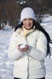 Lächelnde Frau im Winter mit einem Schneeball Stockbild