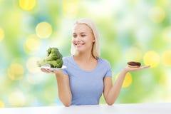 Lächelnde Frau mit Brokkoli und Donut Stockbild