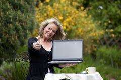 Lächelnde Frau mit dem Laptop, der oben Daumen aufwirft Stockfotos