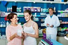 Lächelnde Frau mit Mädchenjugendlichverpackungs-Körperpflegewaren Lizenzfreie Stockfotos