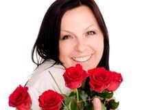 Lächelnde Frau mit roten Rosen Stockbilder