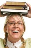 Lächelnde Frau unter Stapel Büchern auf Kopf Stockfoto