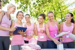 Lächelnde Frauen, die Ereignis für Brustkrebsbewusstsein organisieren Lizenzfreies Stockfoto