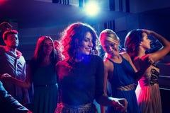 Lächelnde Freunde, die in Verein tanzen Stockfoto
