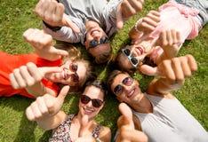 Lächelnde Freunde, welche die Daumen oben liegen auf Gras zeigen Stockfotografie