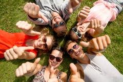 Lächelnde Freunde, welche die Daumen oben liegen auf Gras zeigen Lizenzfreie Stockbilder