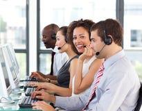Lächelnde Geschäftsfrau, die in einem Kundenkontaktcenter arbeitet Lizenzfreie Stockfotografie