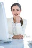 Lächelnde Geschäftsfrau, die an ihrem Schreibtisch arbeitet Lizenzfreies Stockfoto