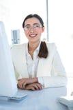 Lächelnde Geschäftsfrau, die an ihrem Schreibtisch arbeitet Stockbilder